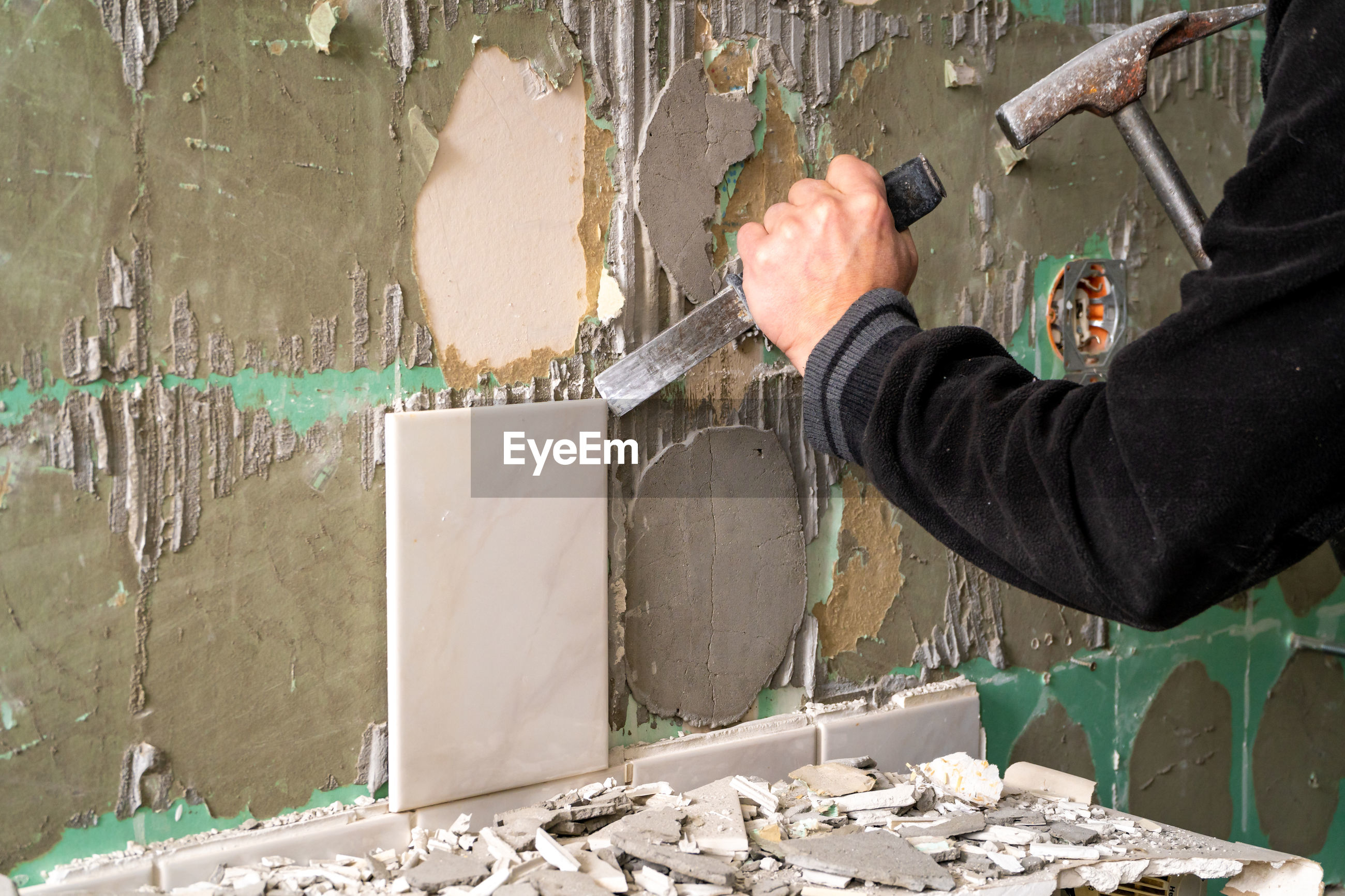 MIDSECTION OF MAN WORKING AT WALL