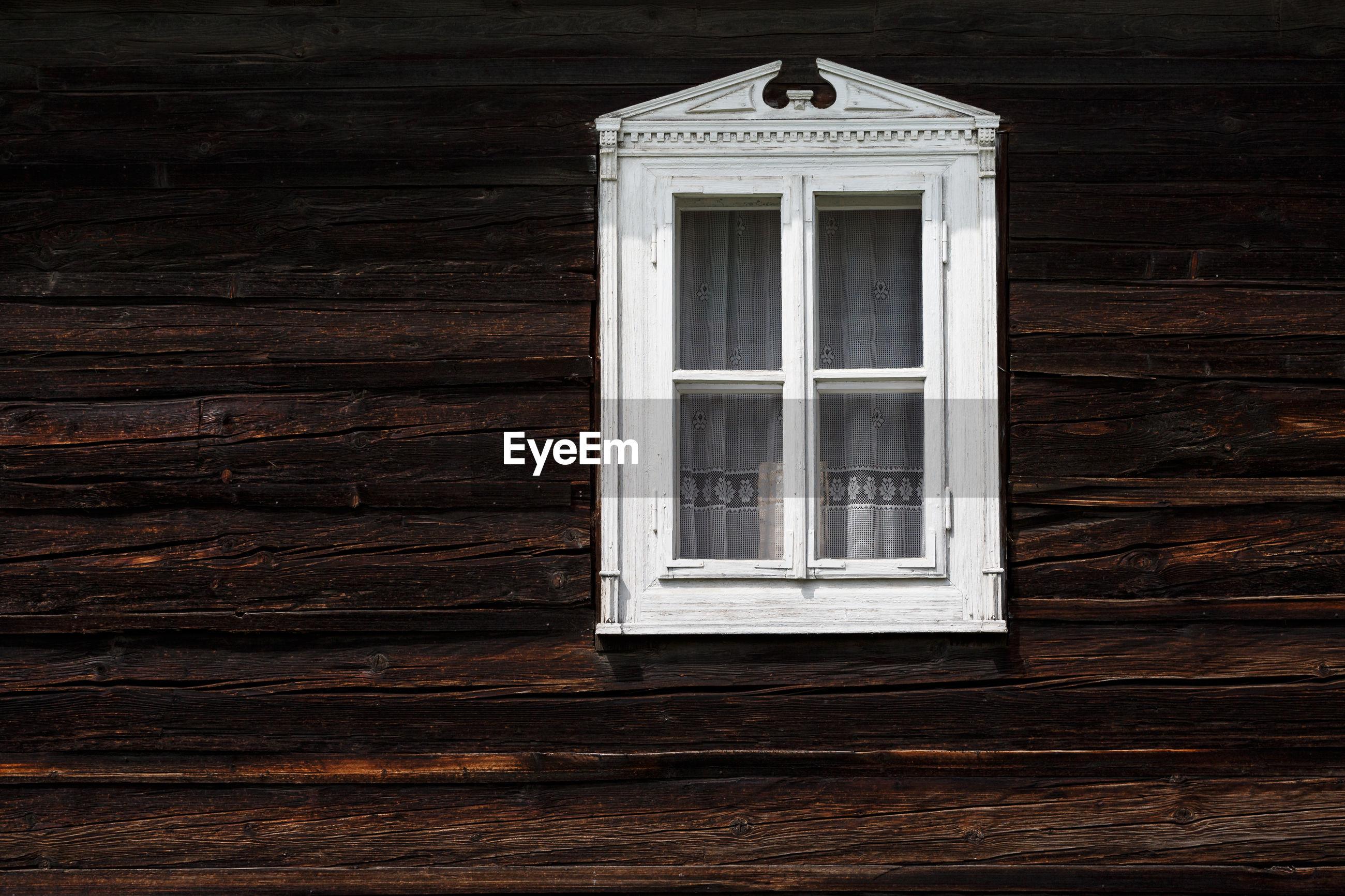 WINDOW ON WOODEN DOOR OF HOUSE