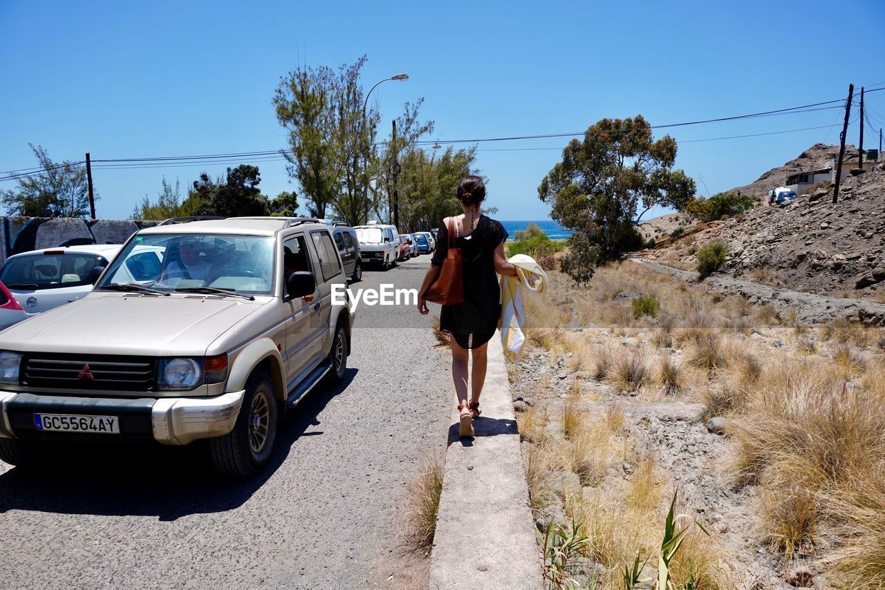 transportation, full length, one person, real people, mode of transportation, car, motor vehicle, land vehicle, casual clothing, sky, nature, road, lifestyles, sunlight, tree, rear view, plant, day, leisure activity, outdoors