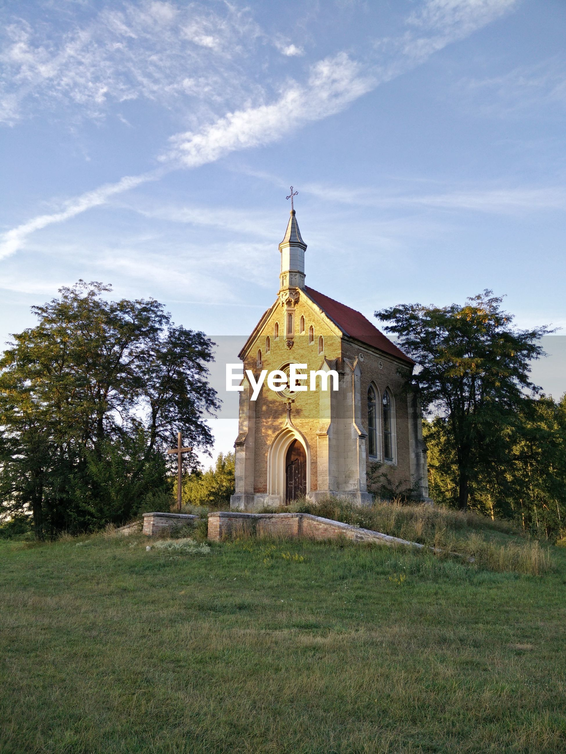 VIEW OF CHURCH WITH TREES IN BACKGROUND