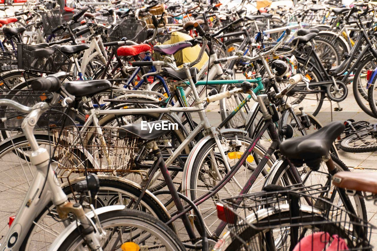 bicycle, transportation, mode of transportation, stationary, land vehicle, large group of objects, day, no people, city, outdoors, abundance, parking lot, cycling, focus on foreground, high angle view, travel, street, close-up, basket, wheel, bicycle shop, spoke, chaos