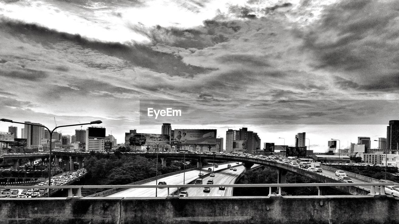 Bridge and buildings against cloudy sky in city