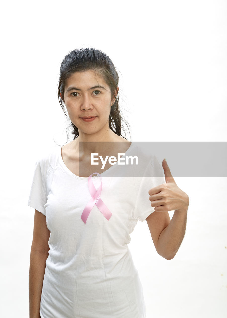 Portrait of smiling woman showing thumbs up while wearing pink ribbon on top against white background