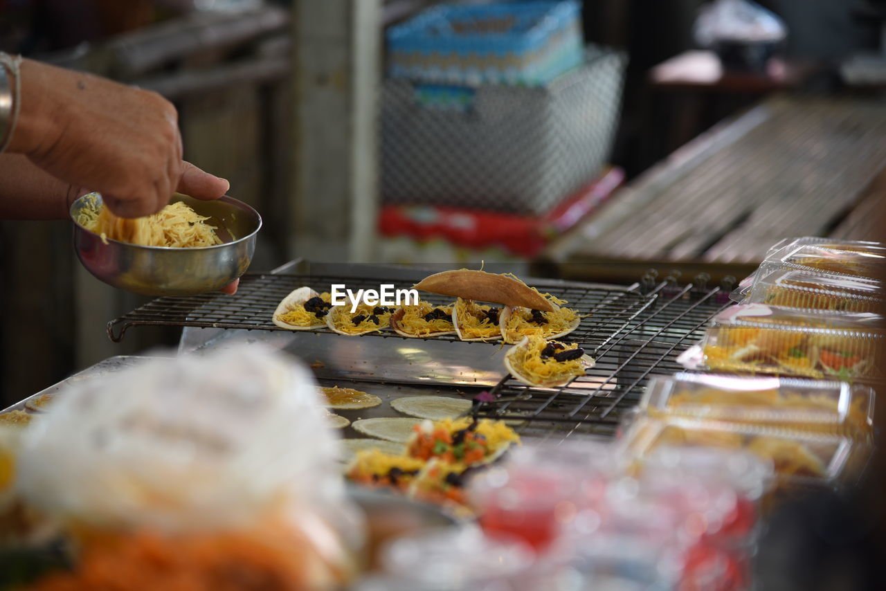 Cropped hand adjusting food on cooling rack