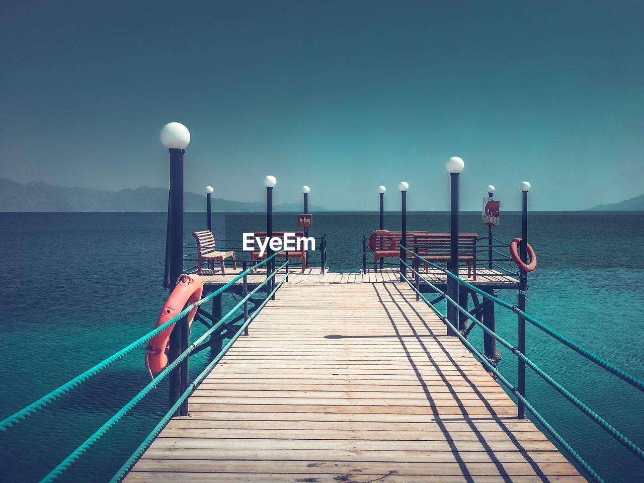 water, sea, sky, pier, direction, nature, railing, blue, the way forward, no people, beauty in nature, clear sky, jetty, tranquil scene, wood - material, tranquility, scenics - nature, day, outdoors, horizon over water, turquoise colored