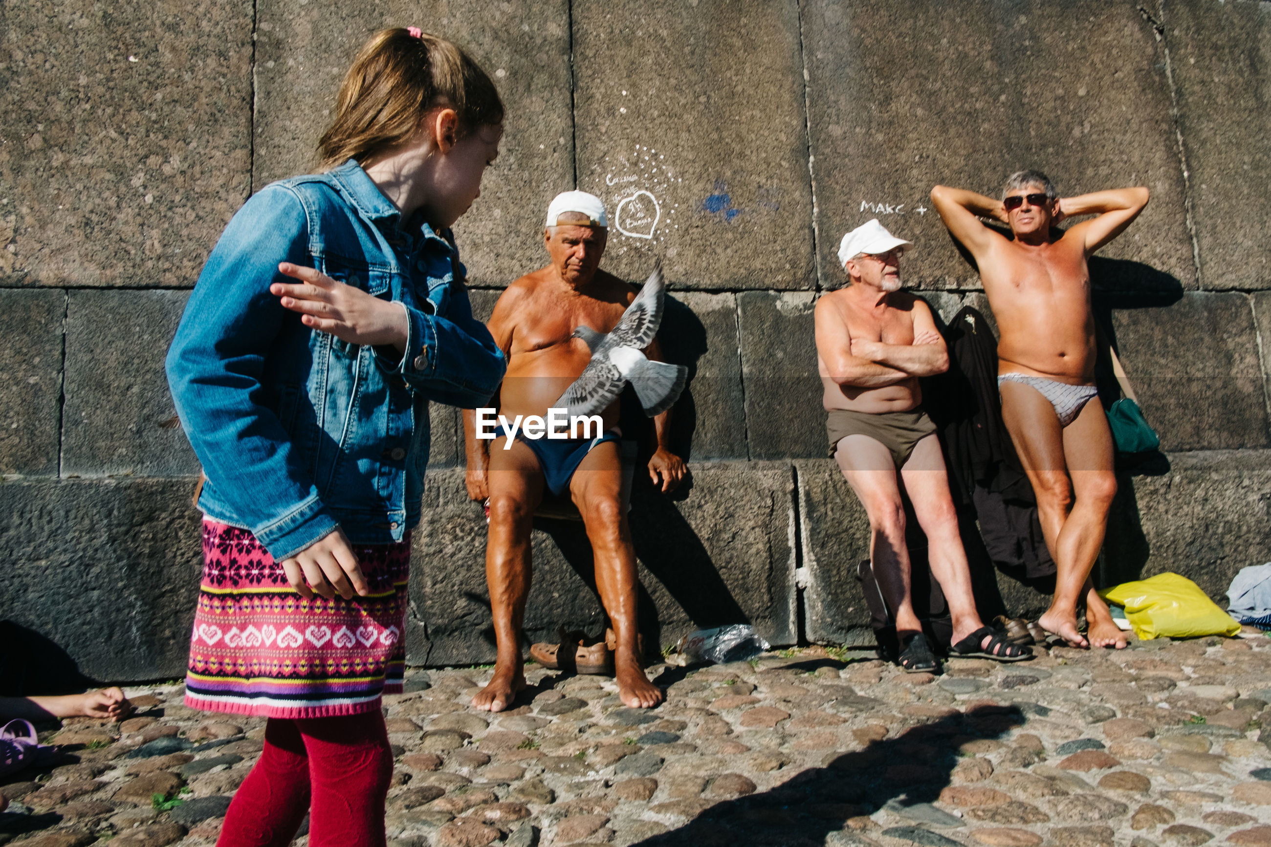 full length, standing, leisure activity, outdoors, shirtless, holding, adult, group of people, sitting, day, people, men, young adult, blond hair, adults only, city