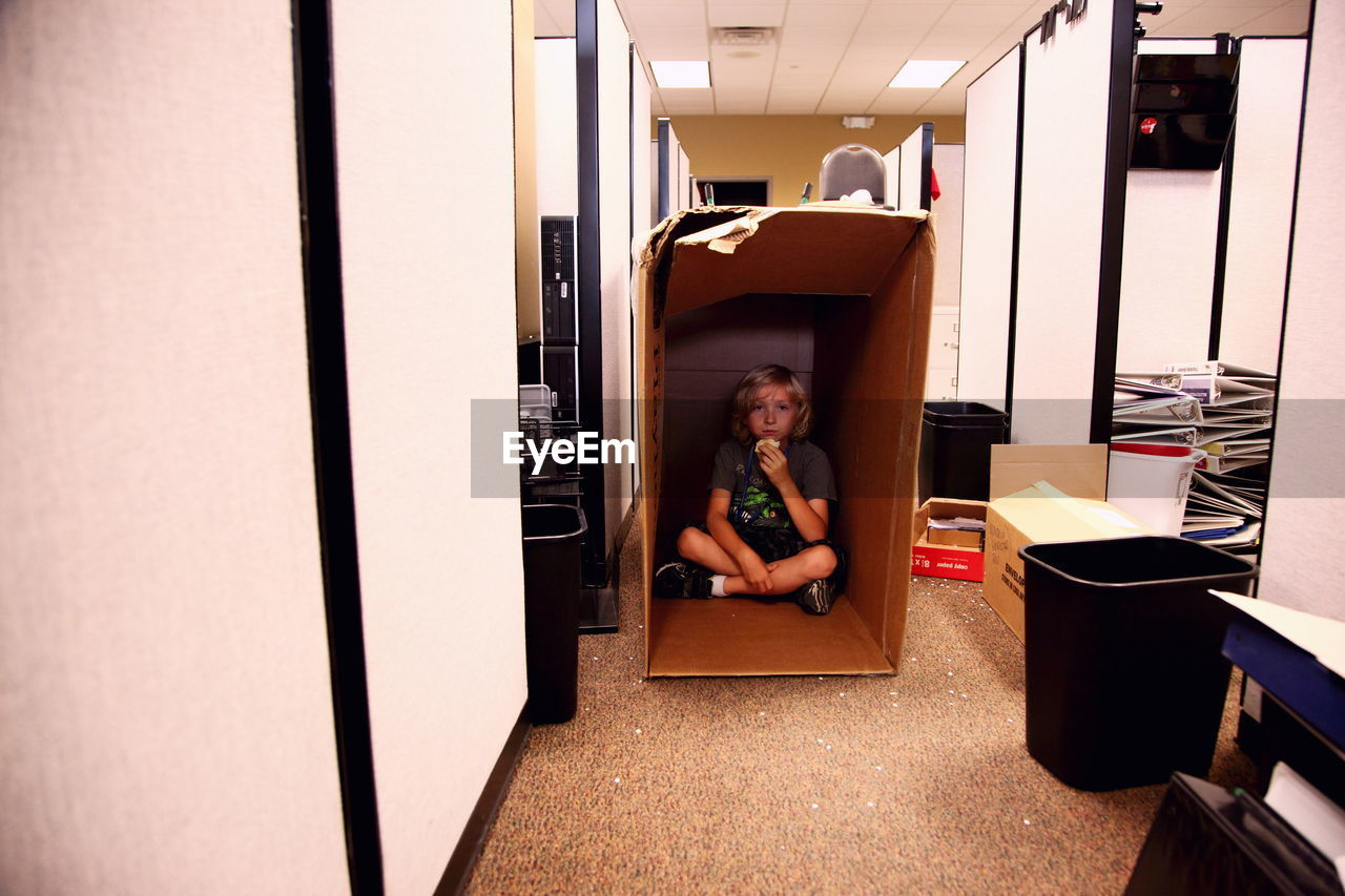 Portrait of boy sitting in cardboard box at office