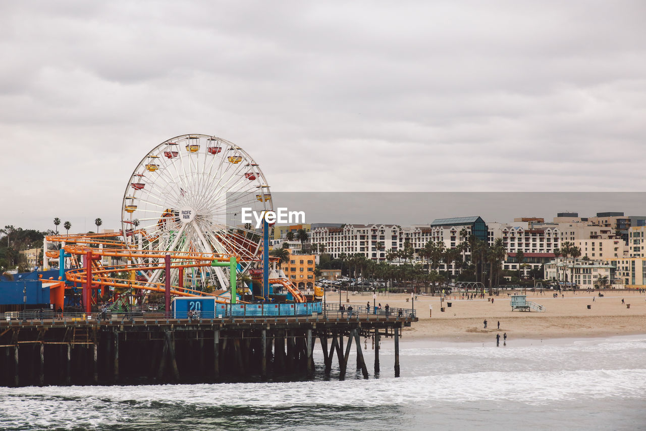 Santa Monica Pier At Beach By Amusement Park Against Cloudy Sky