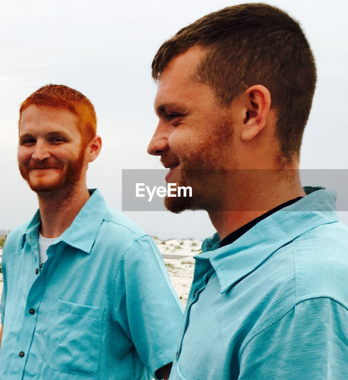 Friends wearing blue shirts standing against sky