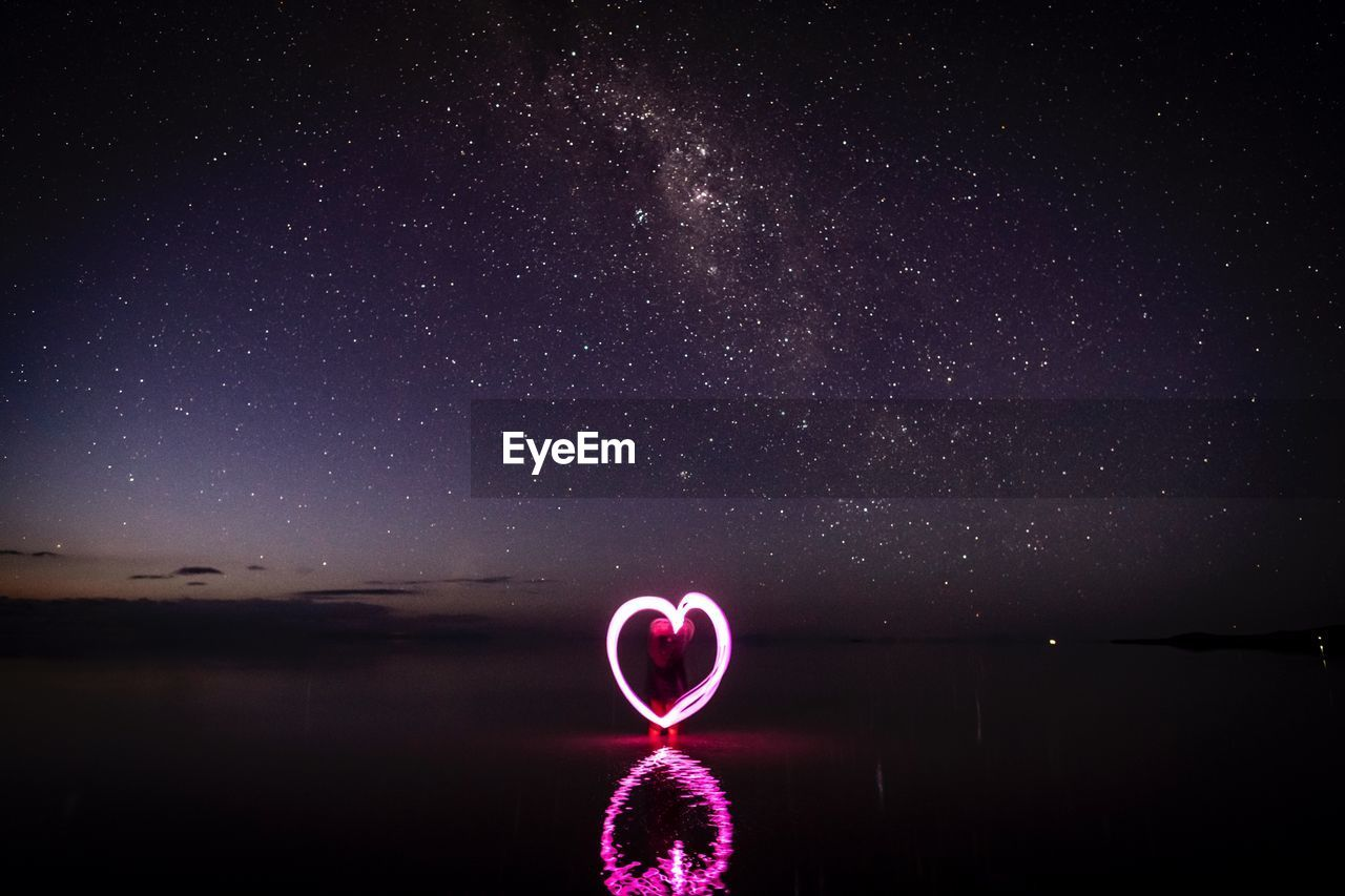 Woman making heart shape with light painting in sea against sky at night