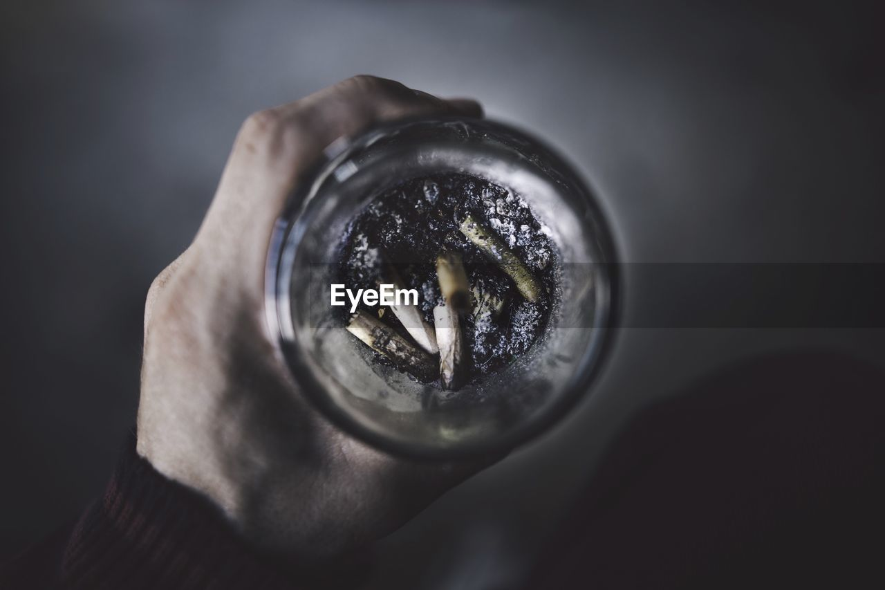 Cropped Image Of Hand Holding Drinking Glass With Cigarette Butts