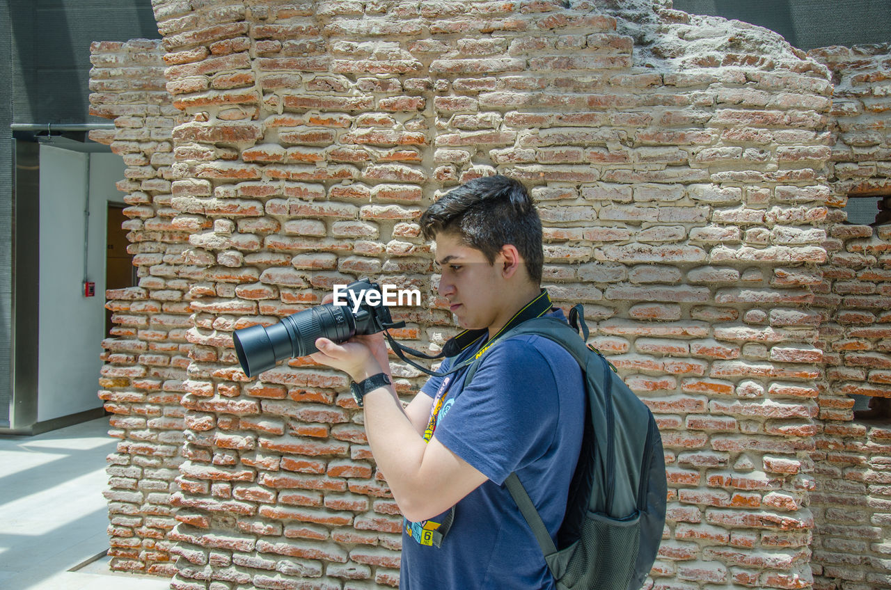brick wall, standing, concentration, gun, holding, one person, side view, day, men, one young man only, outdoors, one man only, males, weapon, adult, people, only men, young adult, adults only