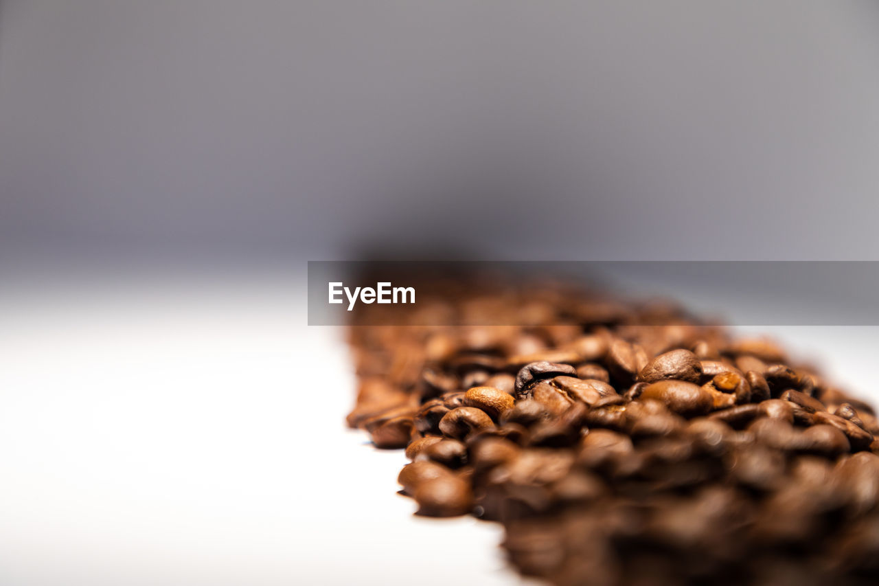 selective focus, still life, food and drink, close-up, indoors, brown, food, studio shot, no people, roasted coffee bean, freshness, copy space, coffee, coffee - drink, table, seed, white background, healthy eating, wellbeing, roasted, caffeine, temptation