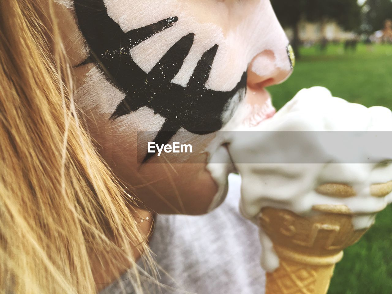 Close-up of girl with face paint eating ice cream