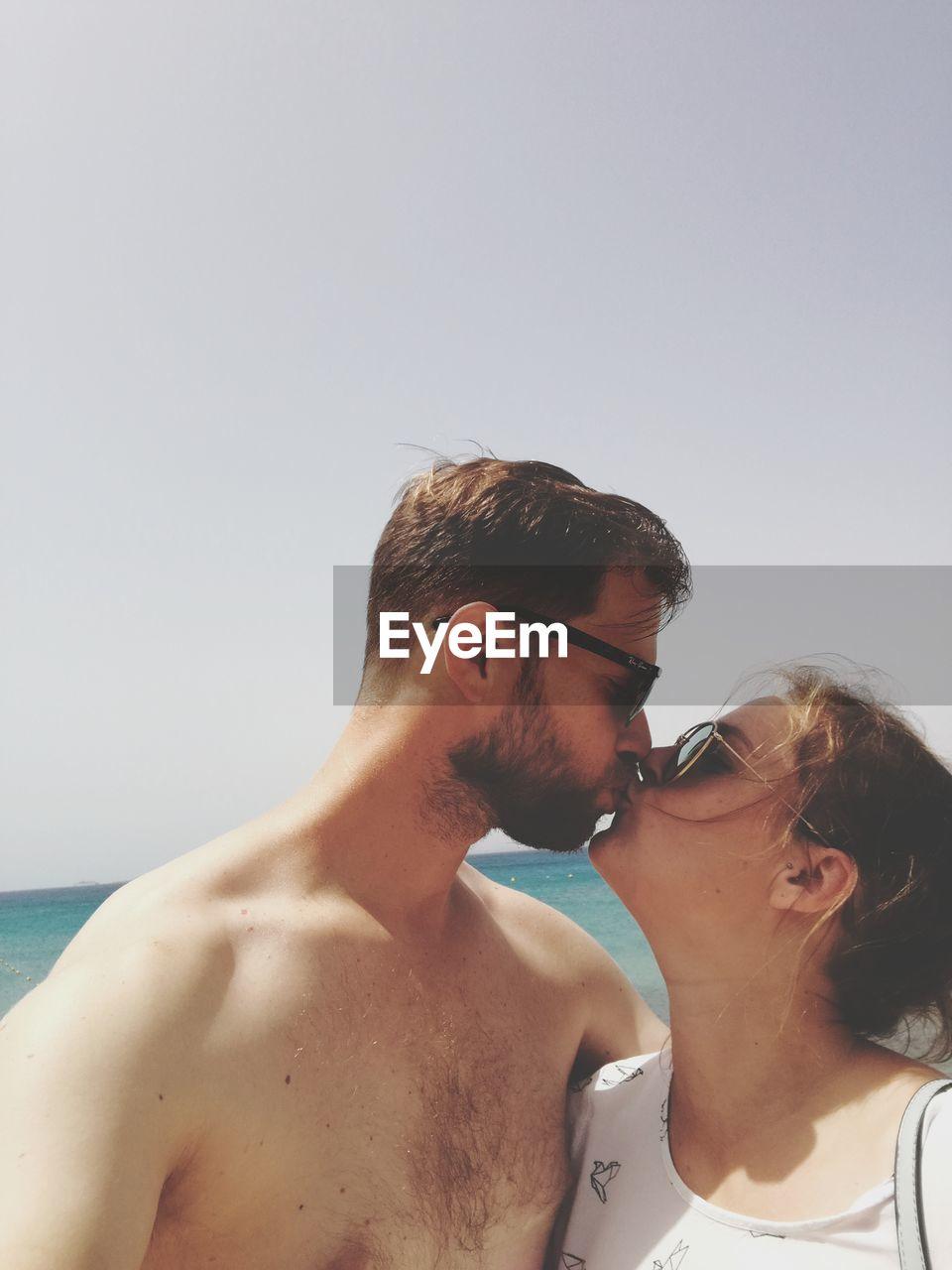 Man kissing woman against clear sky at beach