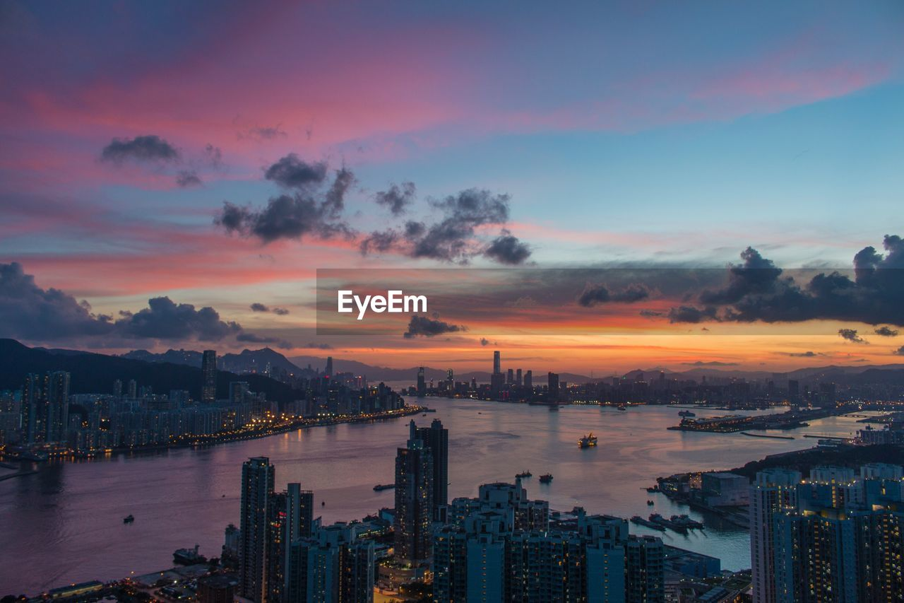 High angle view of river amidst buildings in city at sunset