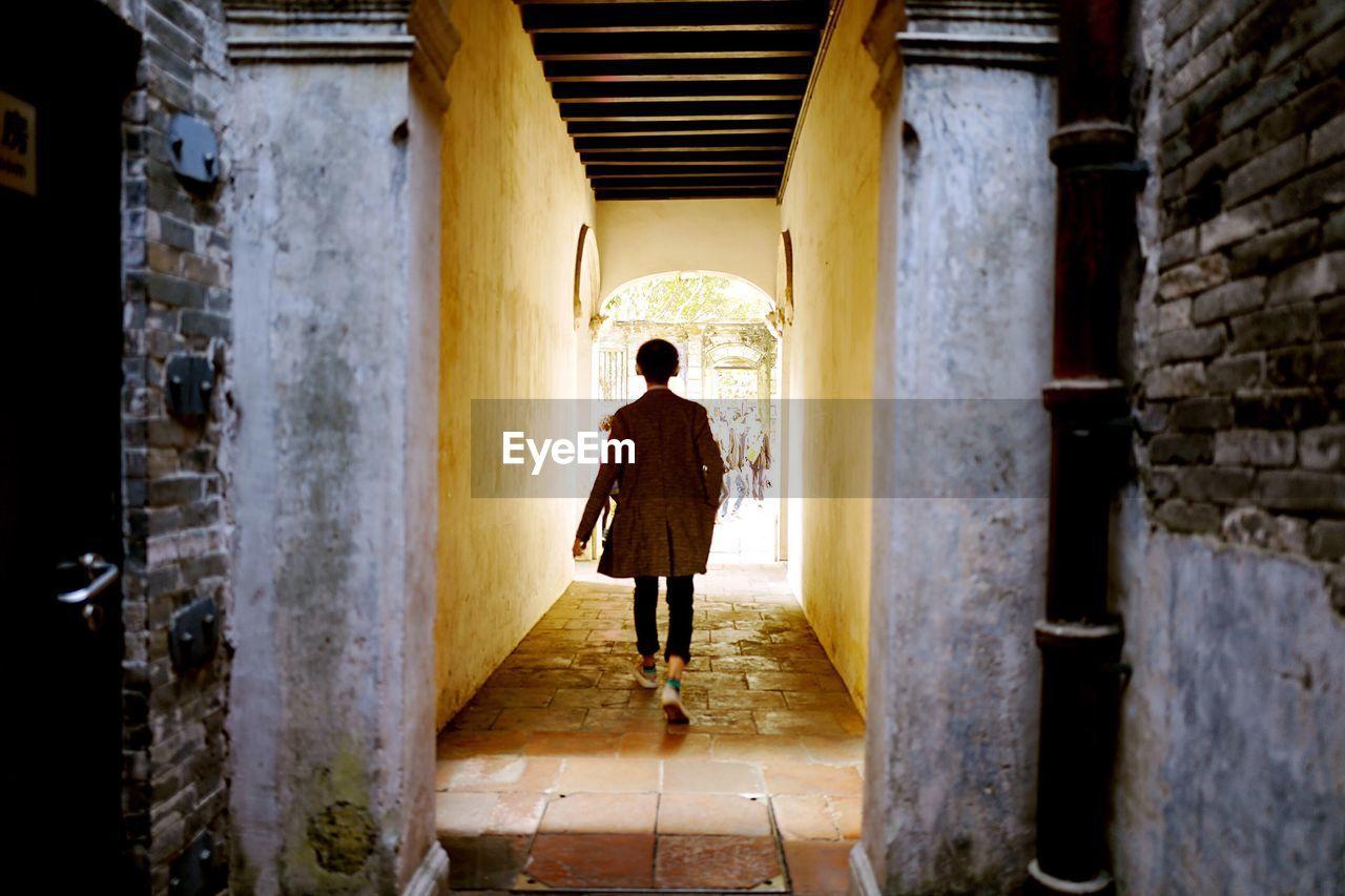 Full Length Rear View Of Man Walking On Narrow Walkway