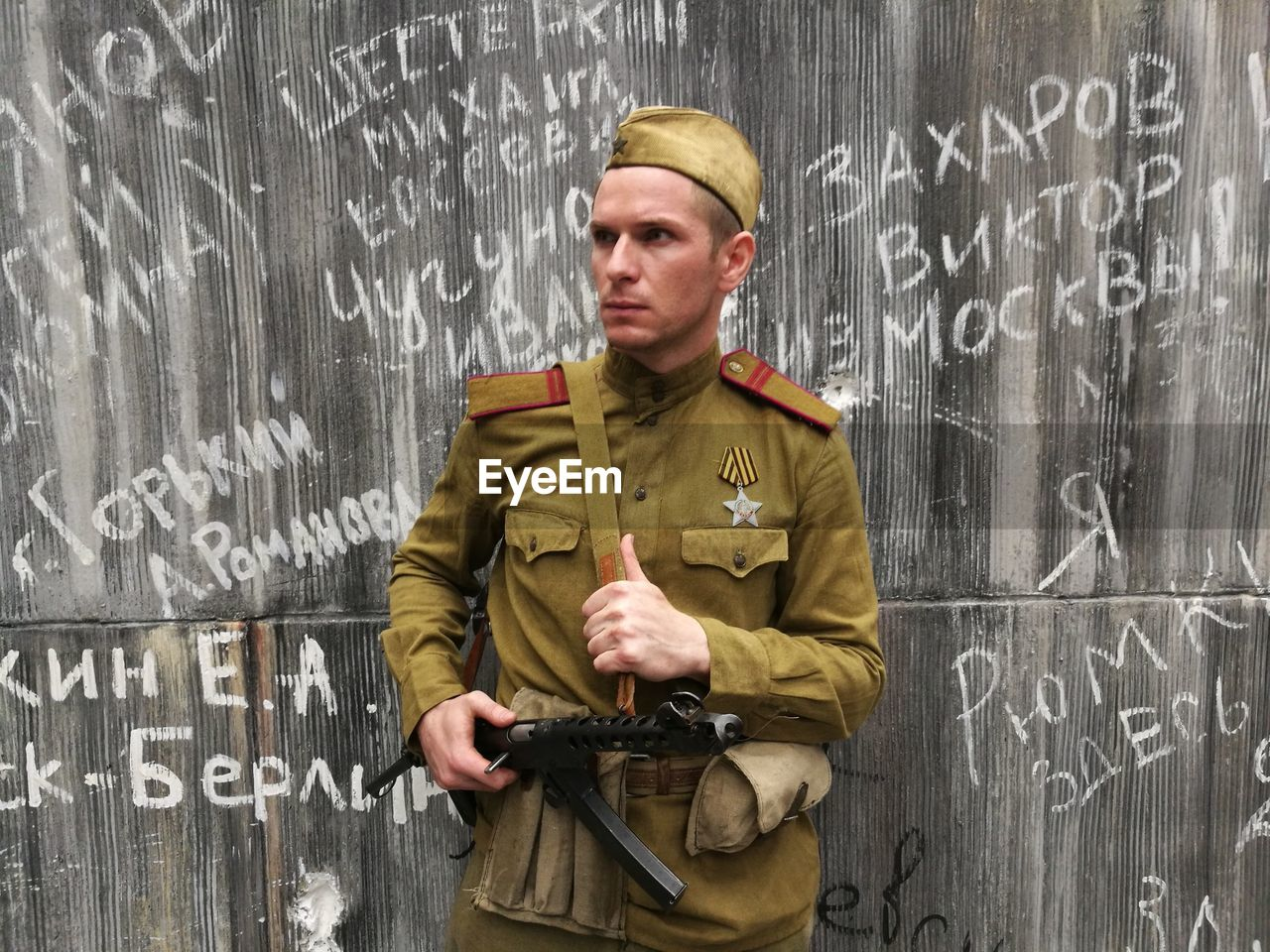 Portrait of army soldier with gun standing against graffiti wall