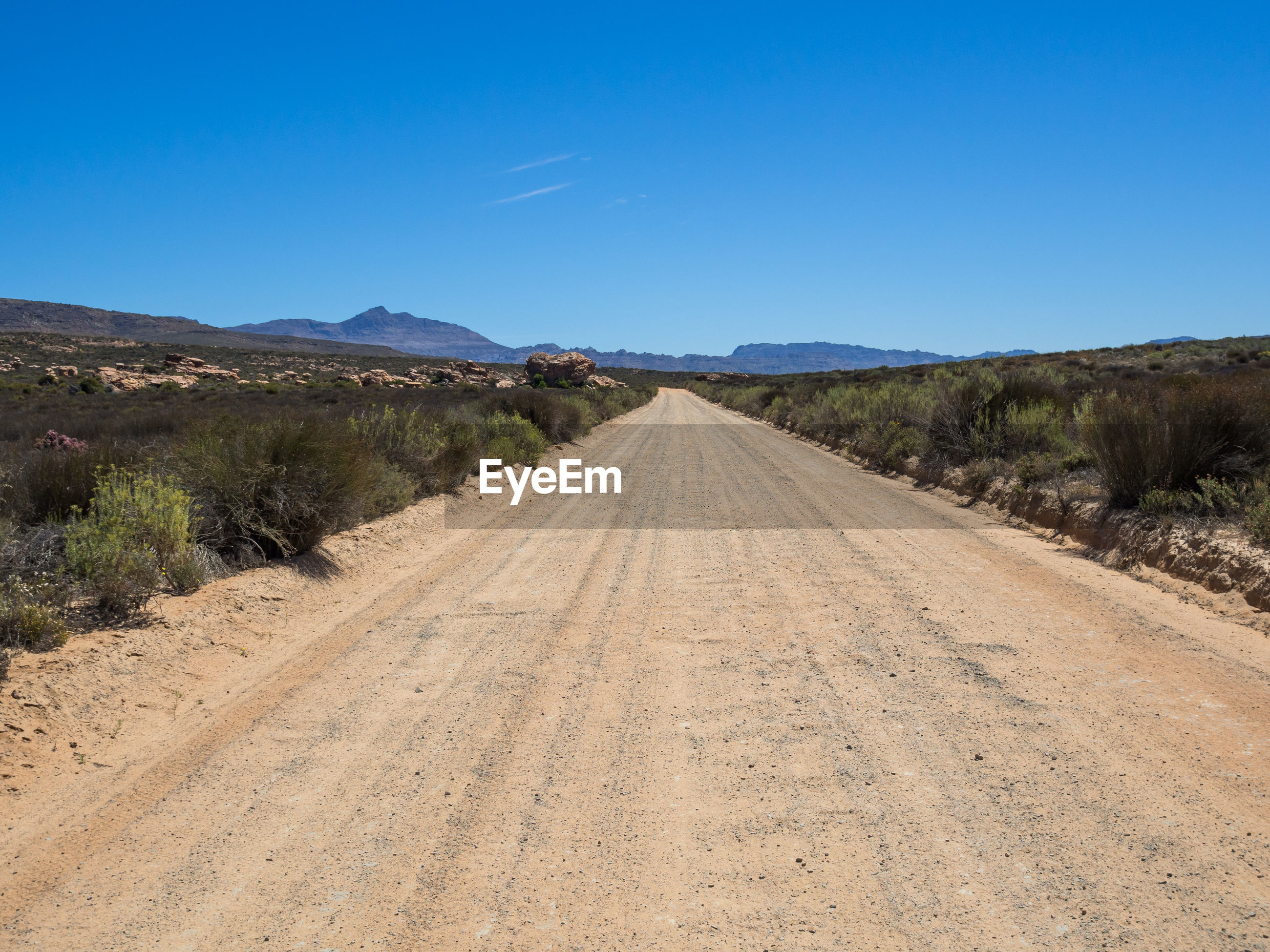 Empty dirt road amidst landscape against clear blue sky, cederberg national park, south africa
