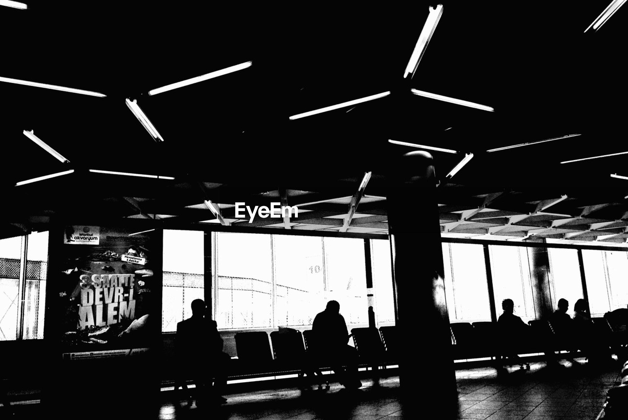 silhouette, indoors, men, lifestyles, illuminated, person, night, leisure activity, standing, airport, medium group of people, built structure, walking, large group of people, group of people, outline, city life, dark