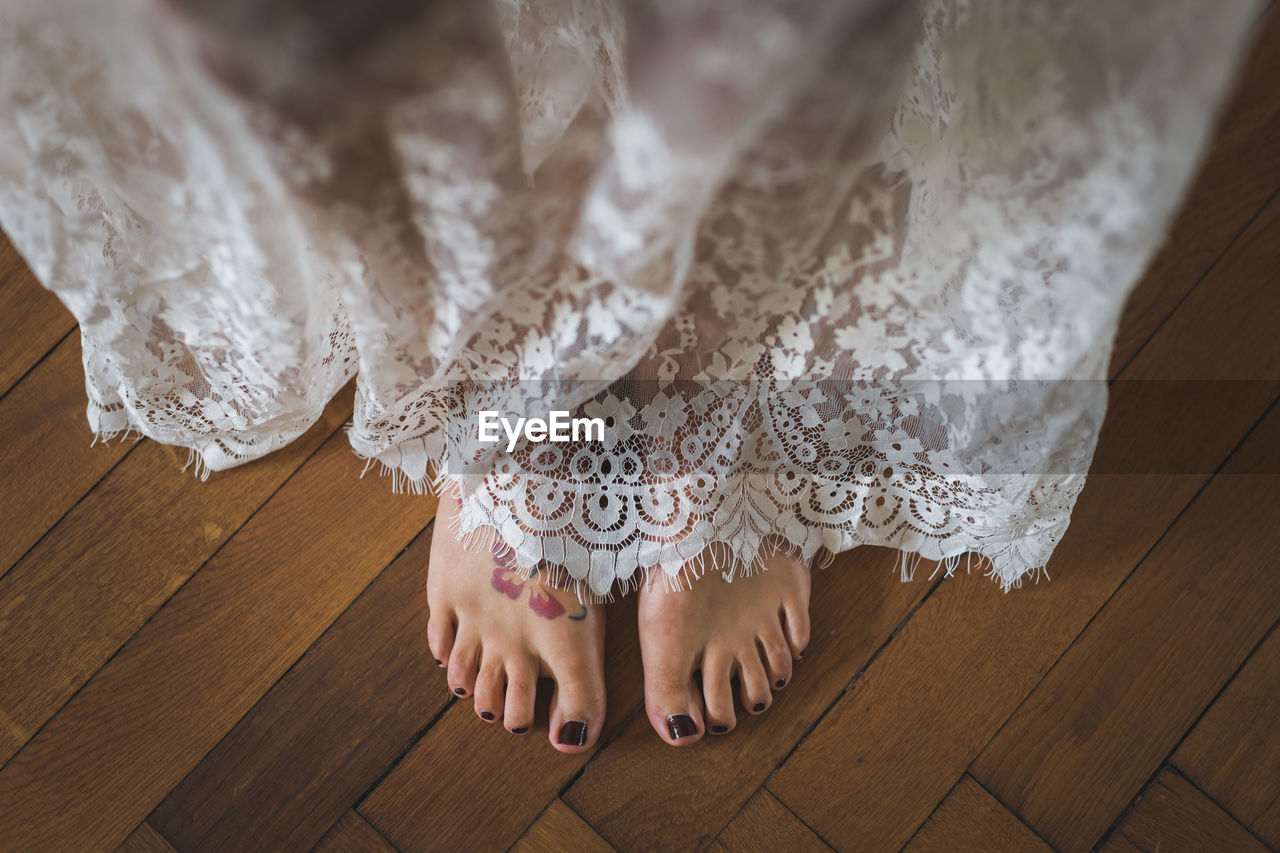LOW SECTION OF WOMAN WEARING CANVAS SHOES ON HARDWOOD FLOOR