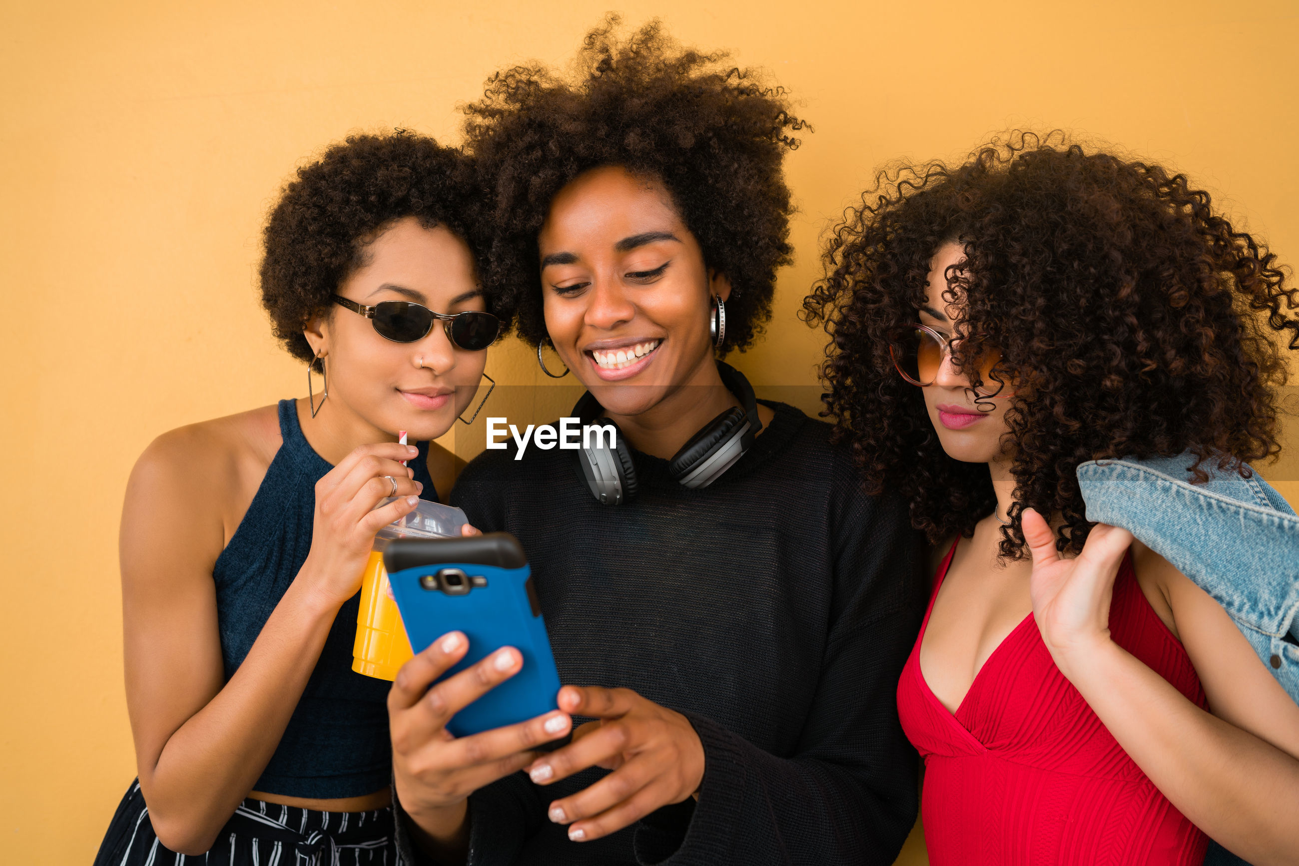 Smiling women looking at smart phone standing by wall