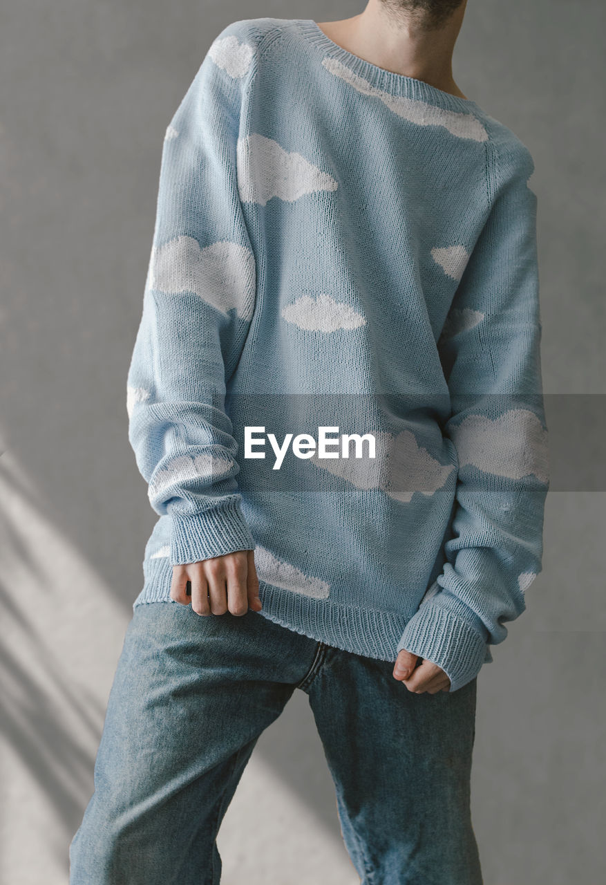 Midsection of man in a sweater with clouds standing against wall
