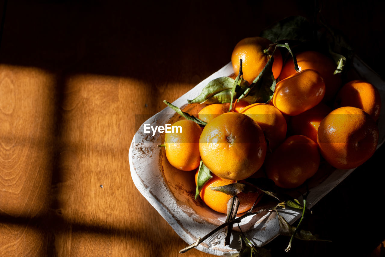 HIGH ANGLE VIEW OF ORANGES IN CONTAINER ON TABLE