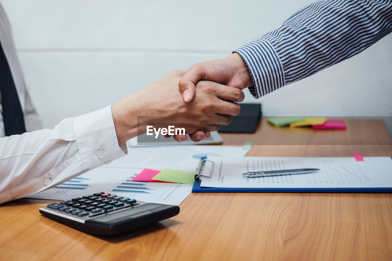 Close-up of business colleagues shaking hands in office