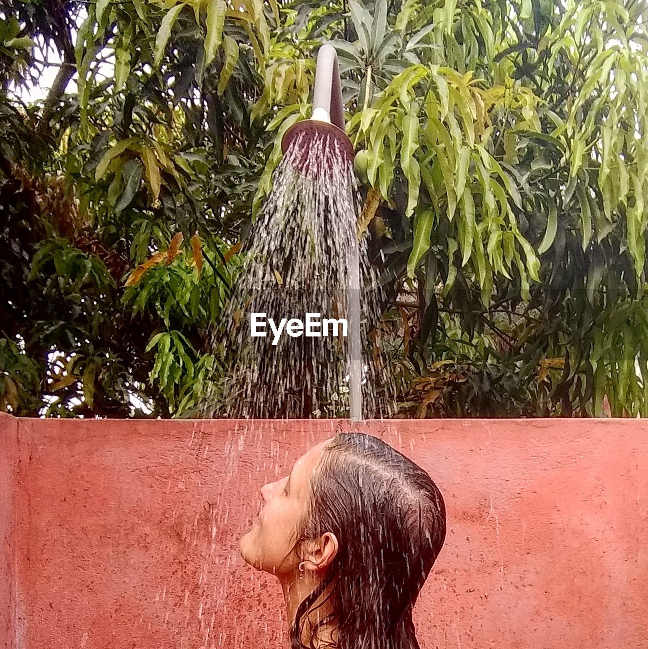 Young woman taking shower outdoors