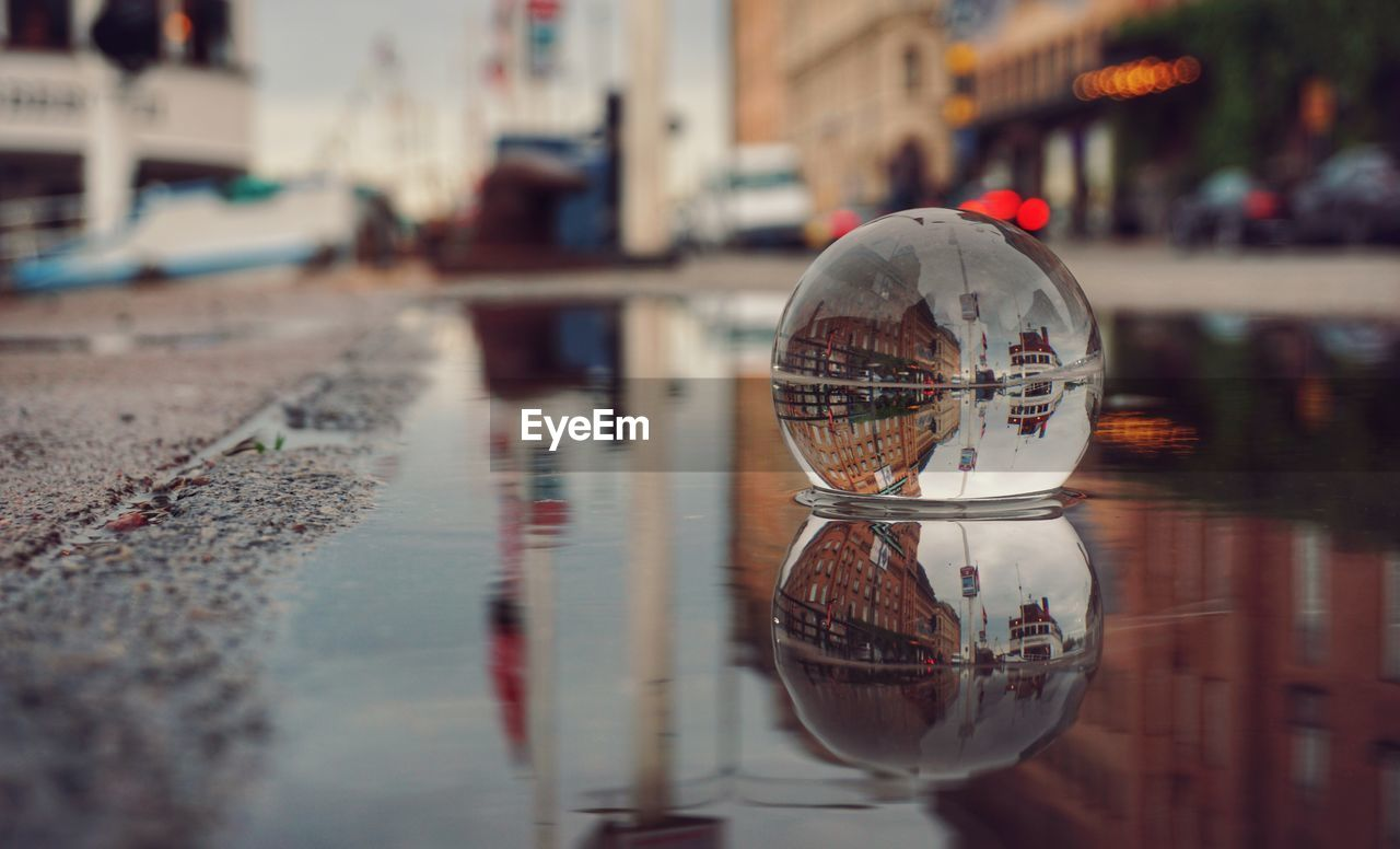 reflection, water, building exterior, city, architecture, incidental people, built structure, transportation, selective focus, mode of transportation, building, glass - material, wet, day, street, car, nature, waterfront, motor vehicle, outdoors, rain, surface level