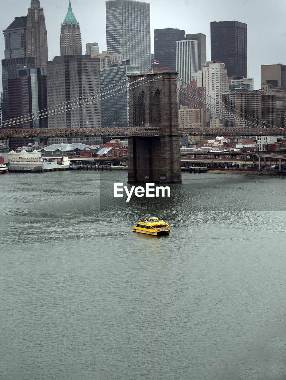 Ferry Sailing In East River By Brooklyn Bridge Against City Skyline