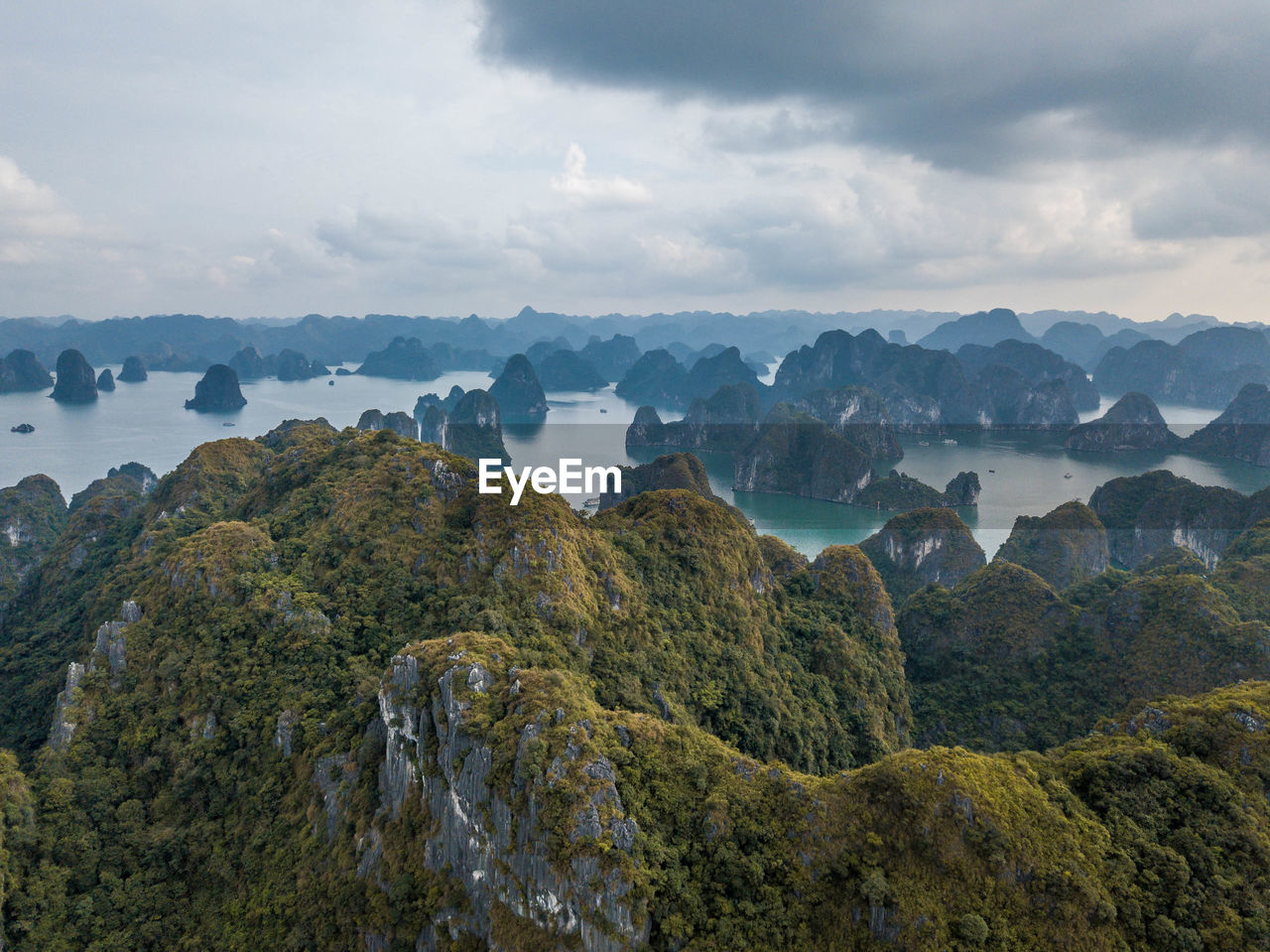 Scenic view of mountains and rock formations in sea against sky