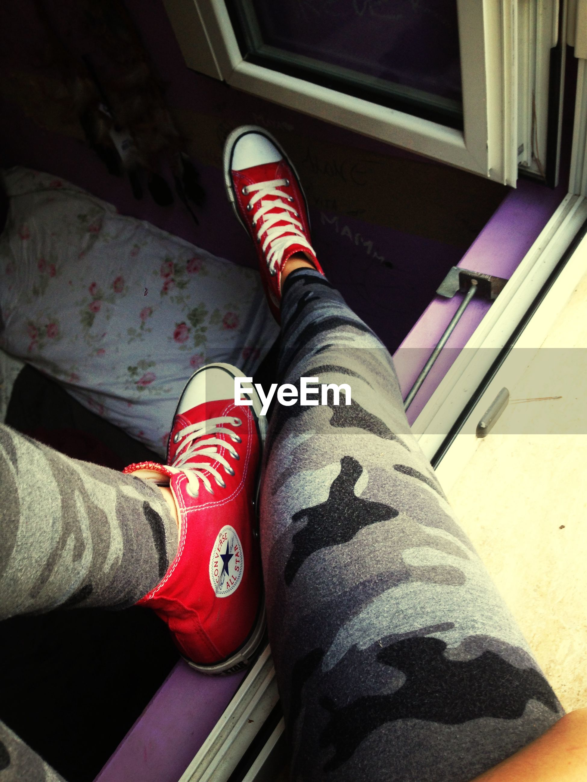 low section, person, shoe, jeans, lifestyles, personal perspective, human foot, footwear, men, leisure activity, indoors, standing, canvas shoe, high angle view, red, sitting, casual clothing