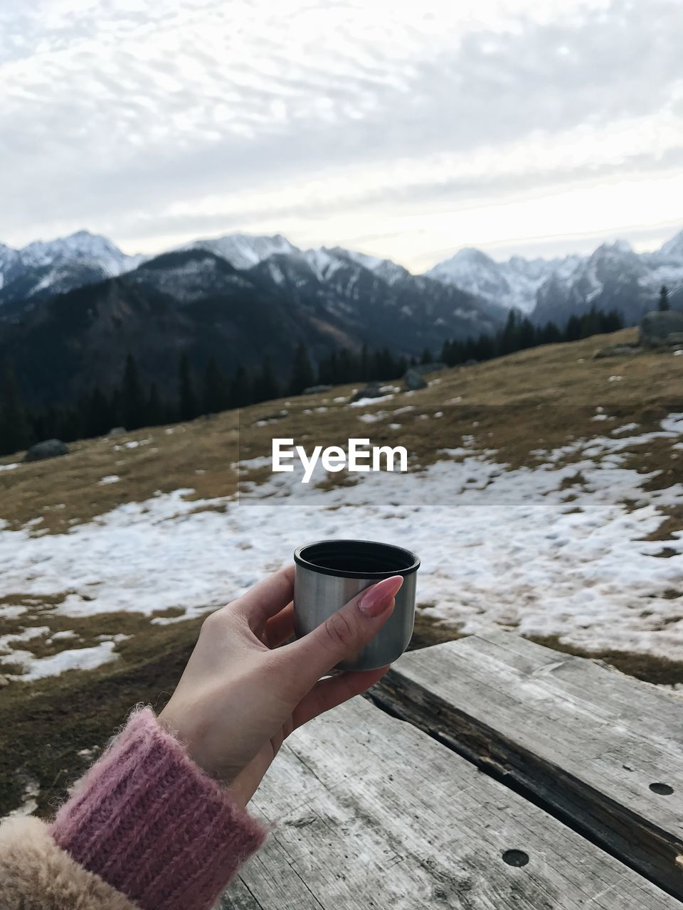 PERSON HAND ON SNOW COVERED MOUNTAIN