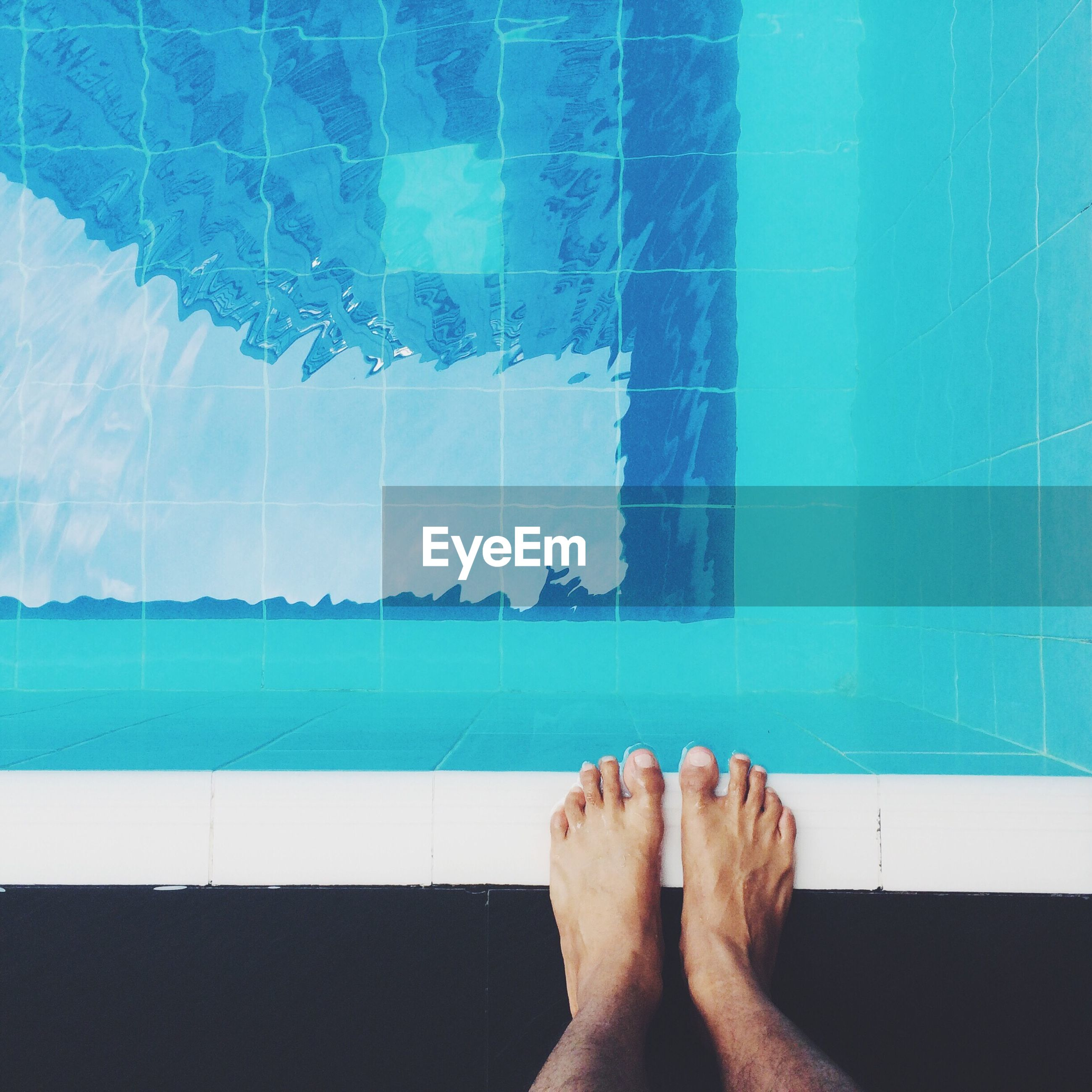 Low section of person standing on poolside
