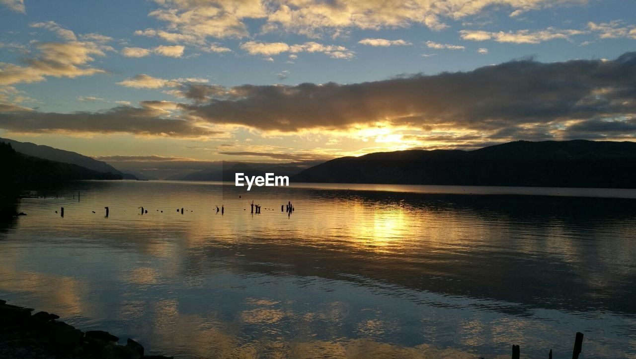 sunset, water, beauty in nature, reflection, scenics, nature, lake, tranquil scene, sky, tranquility, cloud - sky, mountain, silhouette, bird, outdoors, no people, animals in the wild, mountain range, travel destinations, animal themes, swimming, day