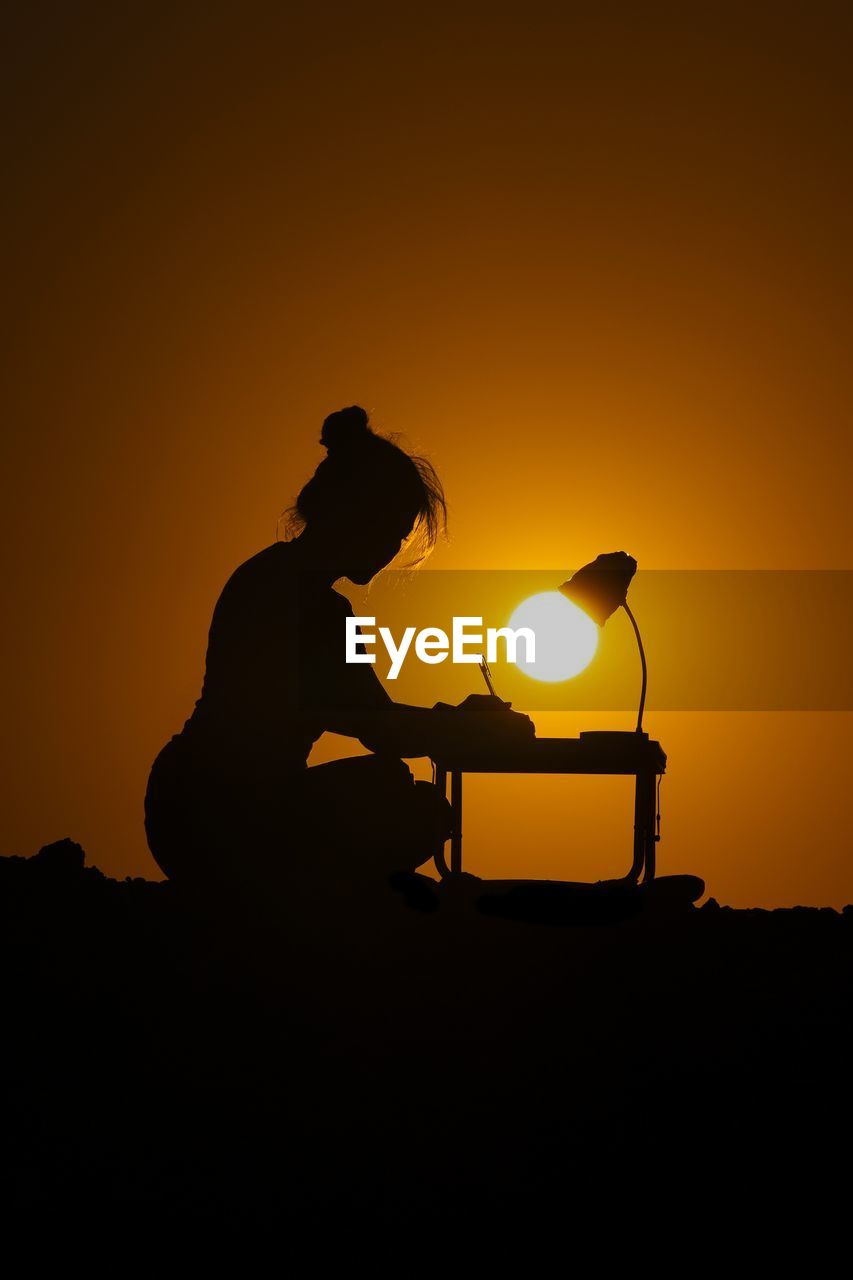 Optical illusion of silhouette woman writing while sitting at table against orange sky during sunset