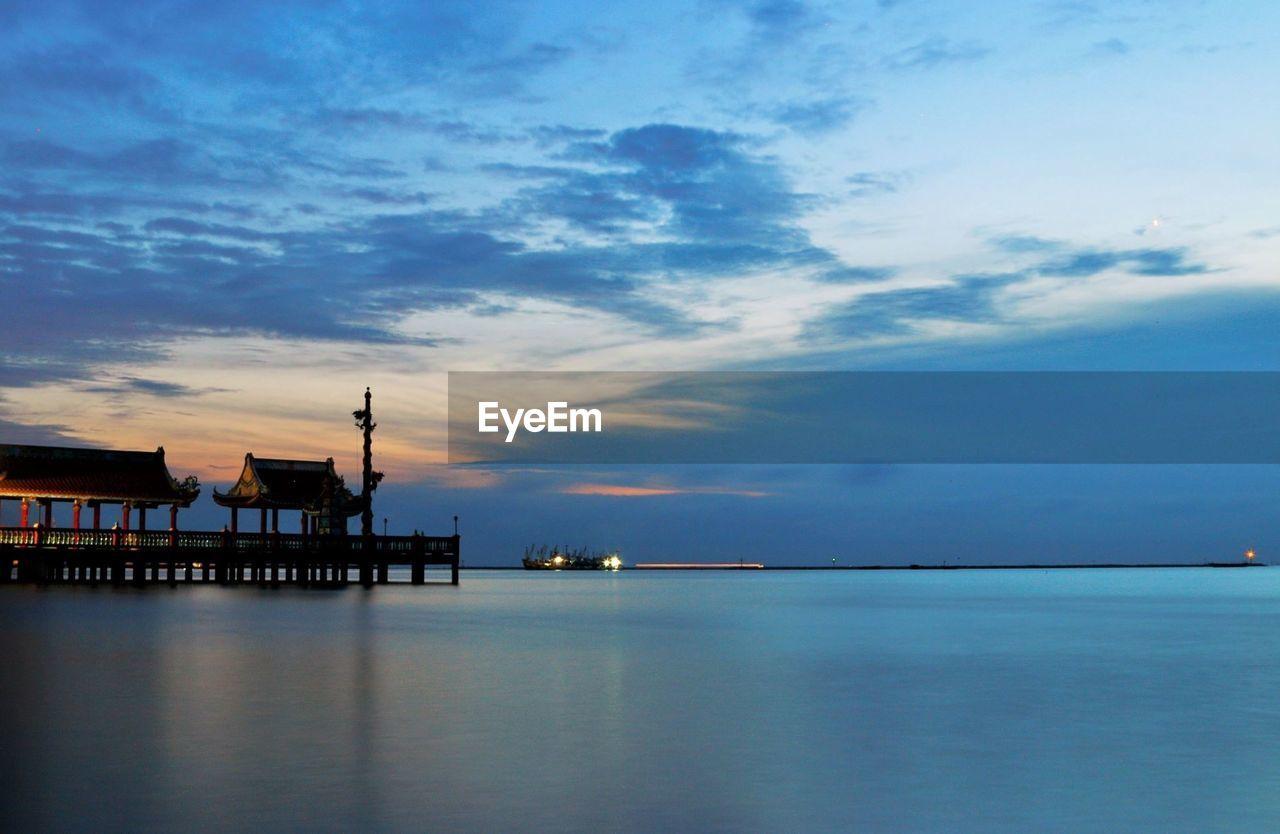 Pier Over Sea Against Cloudy Sky