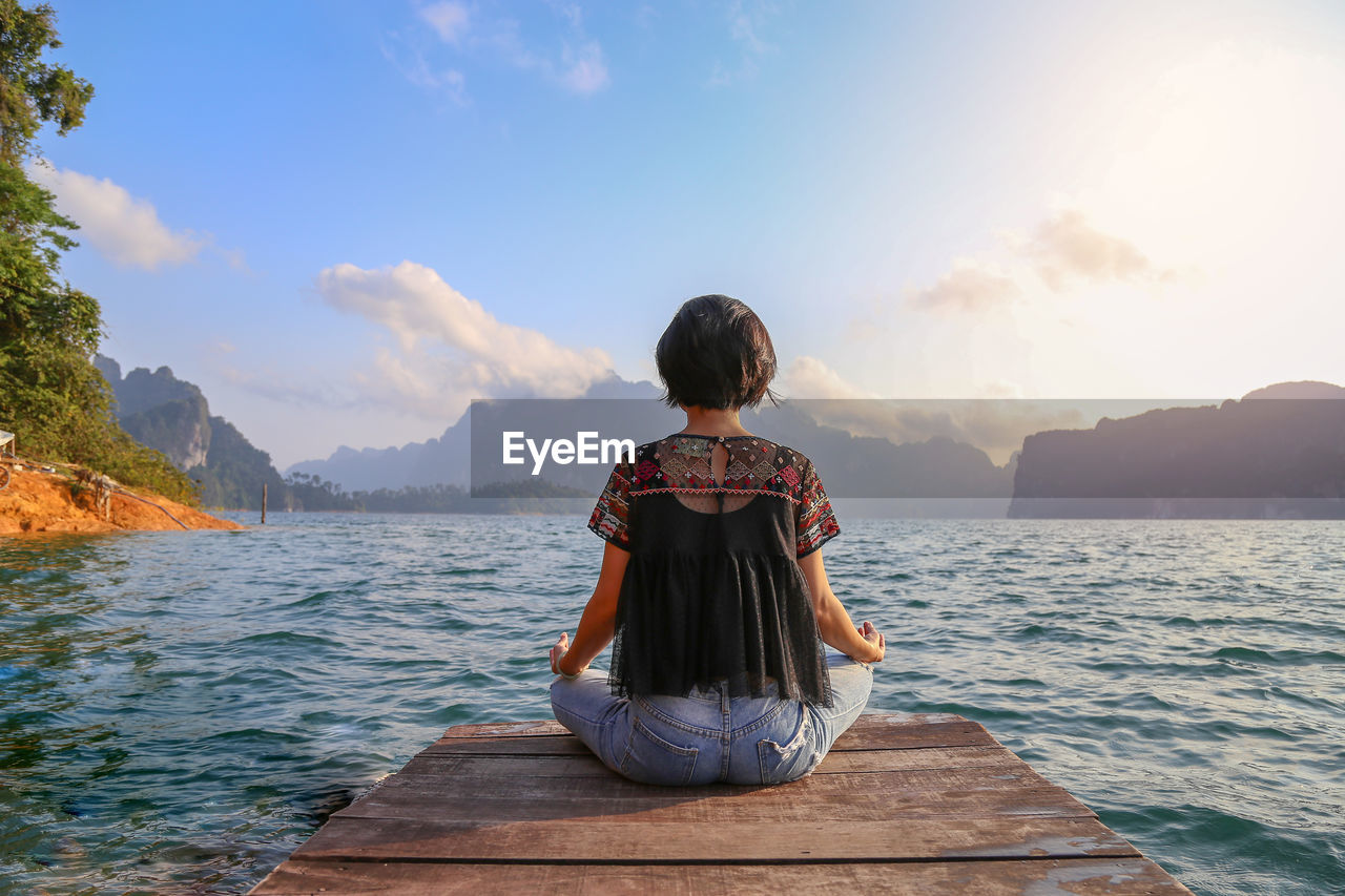 Rear View Of Woman Meditating While Sitting On Pier Over Lake