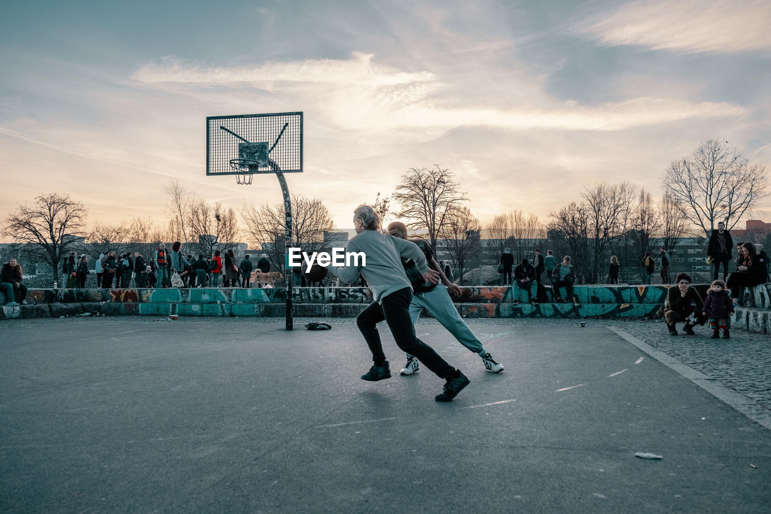 PEOPLE PLAYING BASKETBALL HOOP