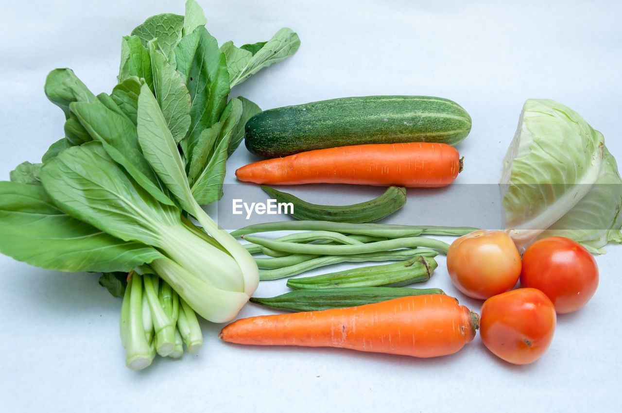 vegetable, healthy eating, food, food and drink, freshness, carrot, wellbeing, green color, raw food, still life, root vegetable, indoors, studio shot, no people, white background, cucumber, close-up, high angle view, group of objects, orange color