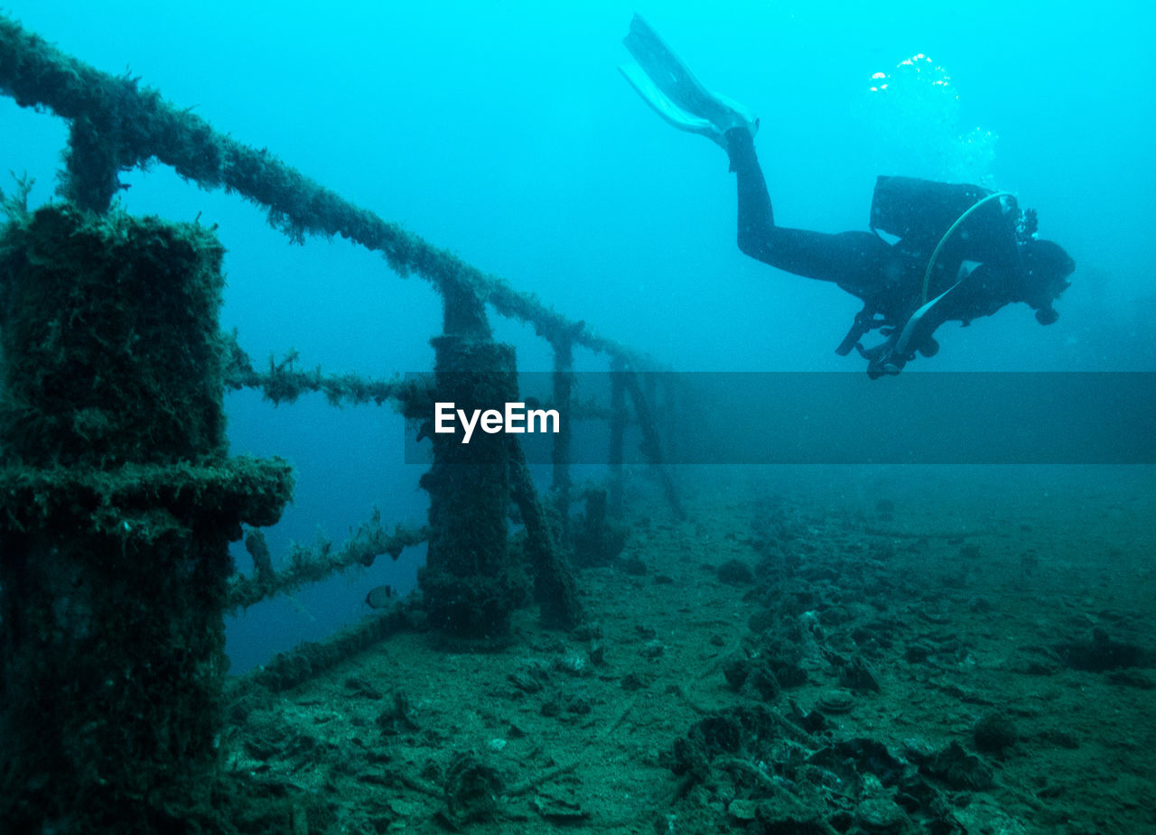 Scuba Diver Swimming By Old Railing In Sea