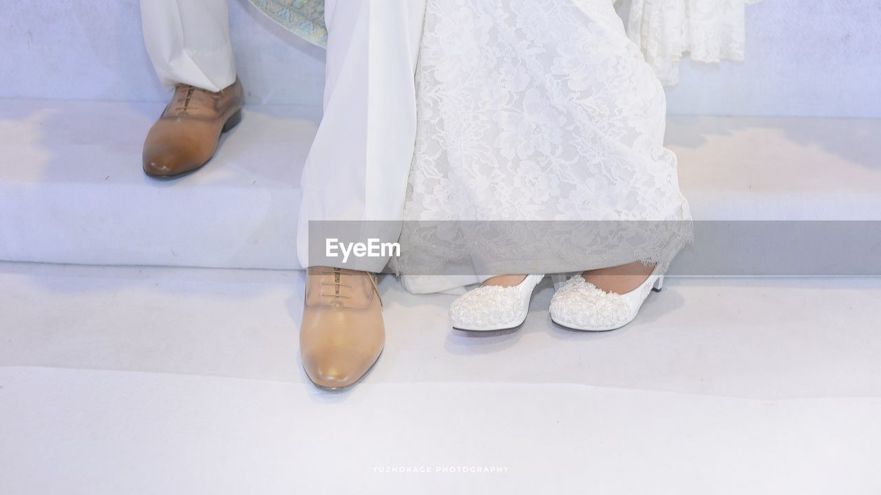 bride, wedding, low section, real people, shoe, wedding dress, life events, human leg, groom, celebration, well-dressed, bridegroom, women, sandal, celebration event, wedding ceremony, standing, indoors, lifestyles, men, togetherness, bonding, sitting, day