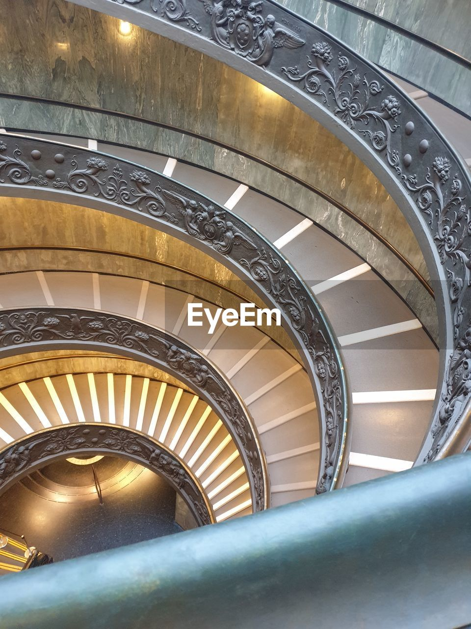 architecture, built structure, railing, steps and staircases, staircase, spiral, indoors, no people, spiral staircase, pattern, low angle view, design, metal, building, day, illuminated, architectural feature, ceiling