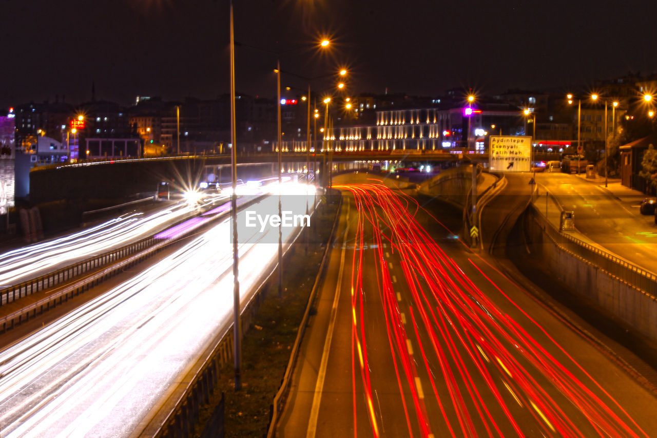 illuminated, night, long exposure, motion, speed, light trail, city, transportation, architecture, street, blurred motion, built structure, road, street light, no people, building exterior, lighting equipment, glowing, high angle view, city life, outdoors