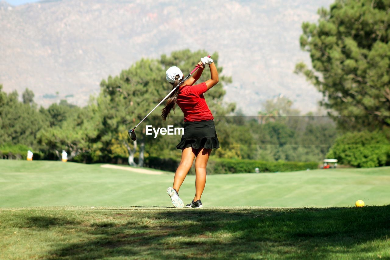 Rear View Of Woman In Sports Clothing Swinging At Golf Course