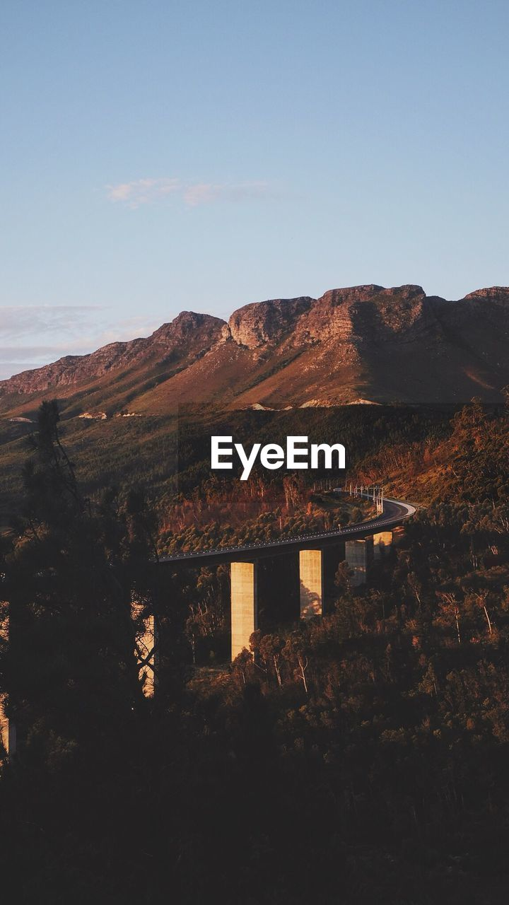 Bridge by mountains against sky