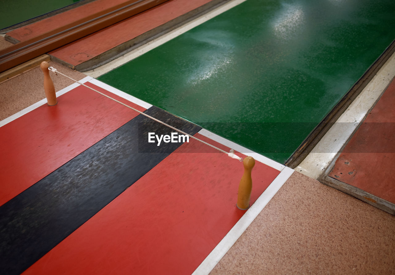 high angle view, sport, no people, water, day, architecture, pool, poolside, red, swimming pool, built structure, outdoors, green color, reflection, absence, nature, court, flooring, wall - building feature, tiled floor