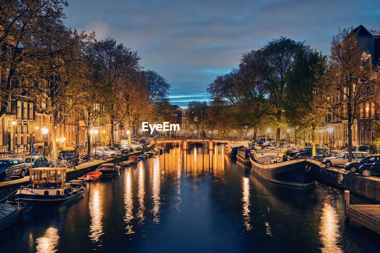 BOATS MOORED ON CANAL IN CITY AT NIGHT